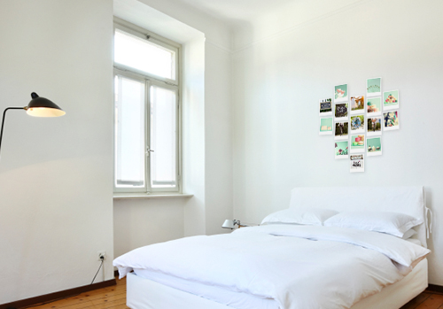 Bed with polaroid photos on the wall