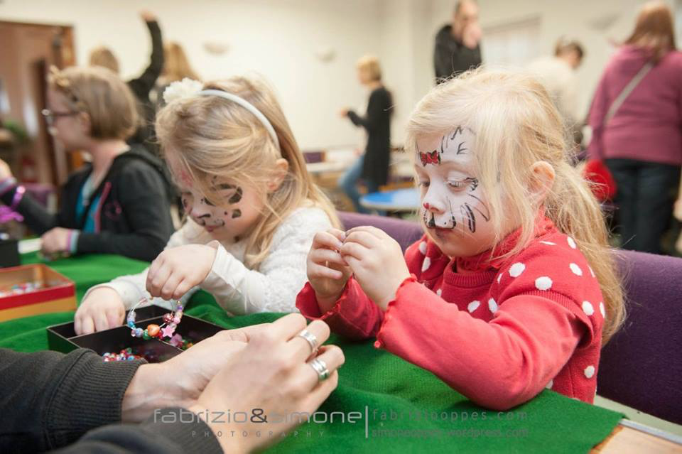 The Fairy Tale Fair: little girls with face painted crafting a bracelet